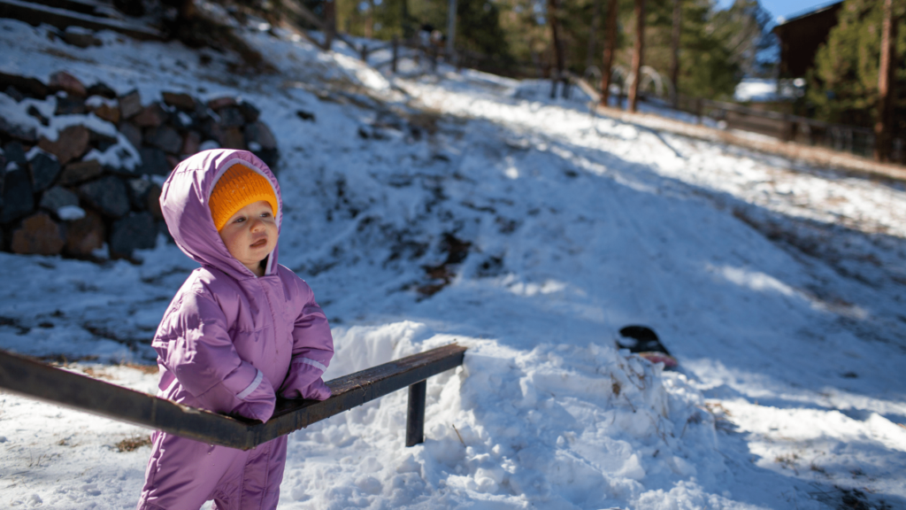 encouraging a small child to play outside in the snow