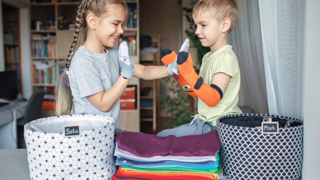 children organizing and folding laundry together