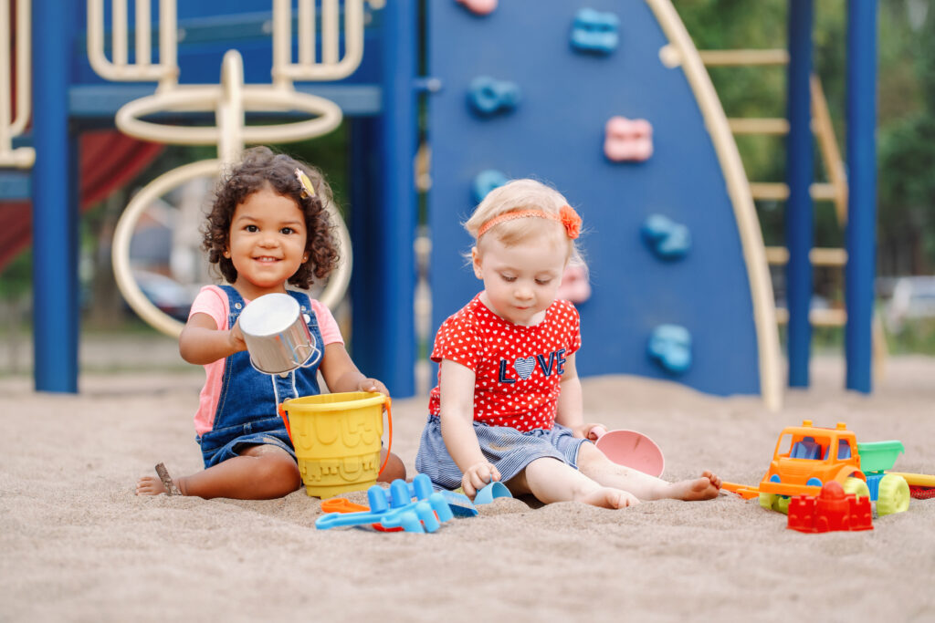 two toddlers sitting in sandbox playing with plastic colorful toys