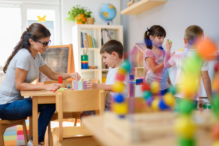 prekindergarten teacher with children playing with colorful wooden toys