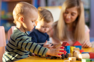 preschool teacher and young toddlers play at daycare