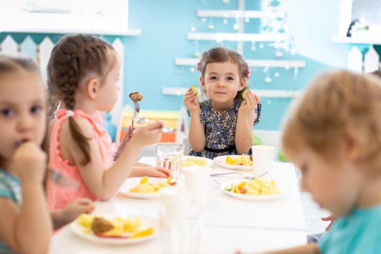 group of kids eating healthy food in preschool