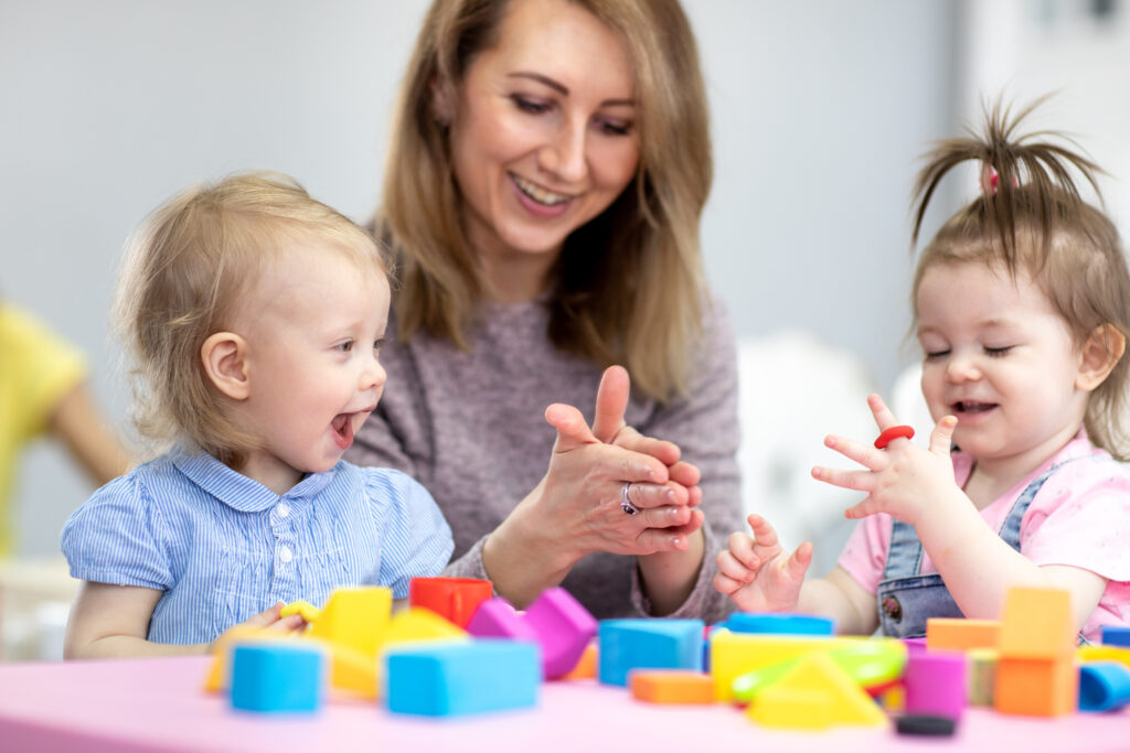 teacher and toddlers play with clay toys at day care center