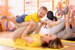 teacher playing airplane with young toddler at daycare