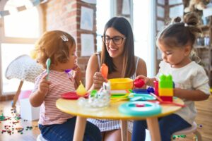 teacher and toddlers playing dinner party at daycare